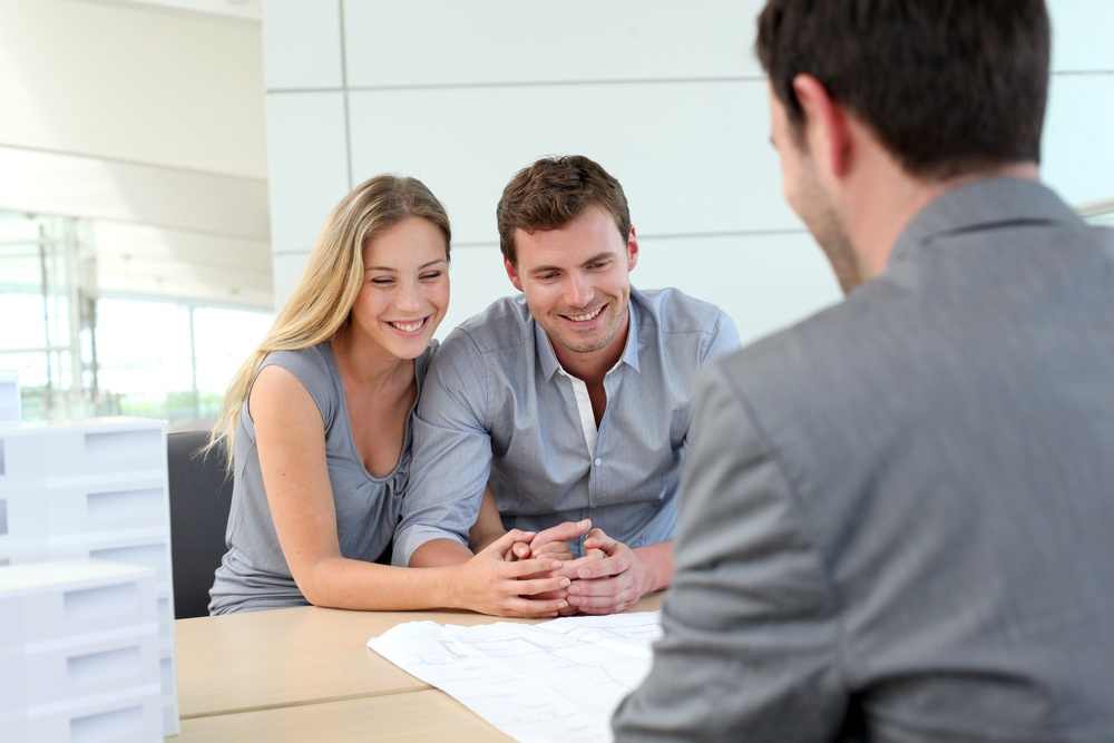 Couple in real-estate agency talking to construction planner.jpeg